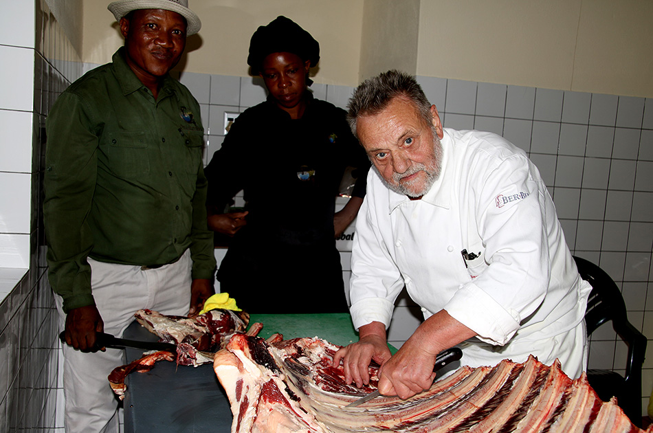 Retired chef trainer Georg Maeding shows manager and chef Fanie Hawanga and cook Wilbertina Nampala how to professionally unflesh cattle ribs